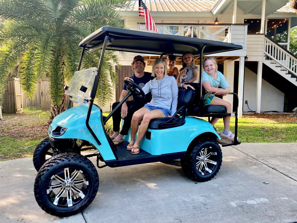 family riding golf cart at isle of palms sc